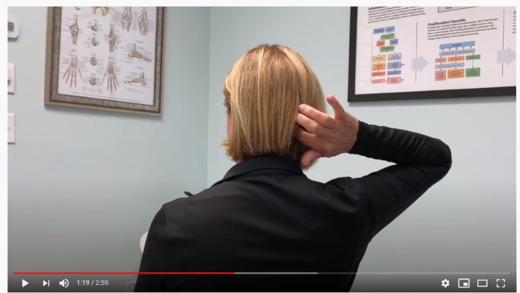 In this screenshot from the video, the patient says: I press here on my C1 area I can get that same sensation as if I'm moving my head, it's very weird thing. Everything bounces. If I could immobilize my head everything would be okay, but when I start walking, every step I take, everything bounces.